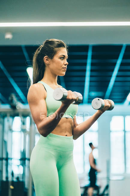 Young athletic woman in sportswear training and concentrated on lifting dumbbells in gym — Stock Photo