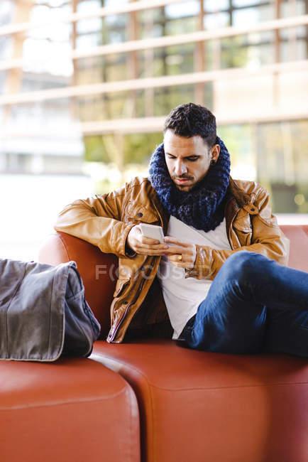 Людина в модному спорядження перегляд смартфона, сидячи на зручному шкіряний диван — стокове фото