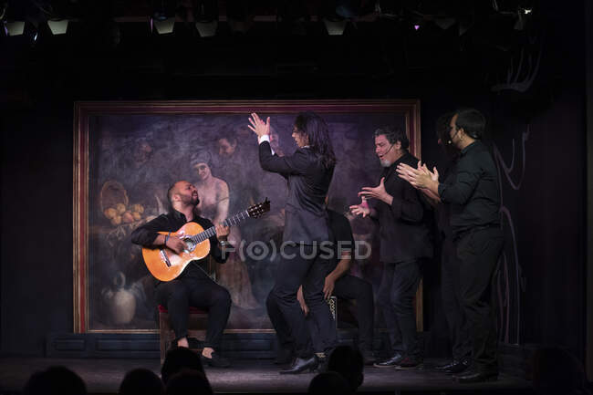 Man in black costume dancing flamenco near Hispanic male musicians during performance against painting on dark stage — Stock Photo