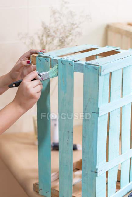 Жіночі ручки для фарбування дерев'яних коробів синього кольору з пензликом — стокове фото