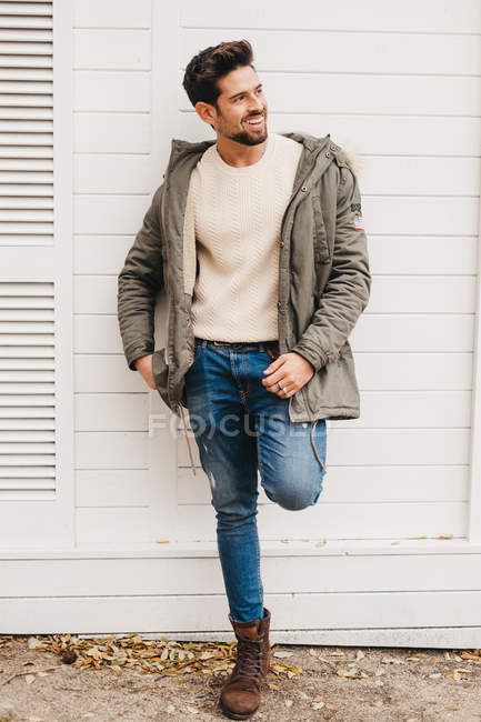 Trendy young man in jeans, boots and parka leaning on white wall and smiling outdoors — Stock Photo