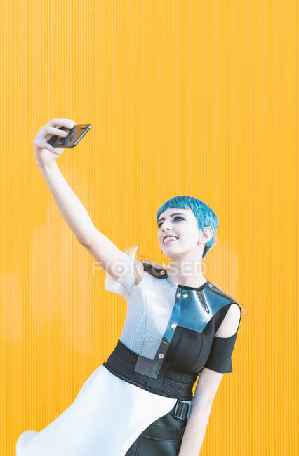 Young woman in futuristic dress laughing and taking selfie with phone while standing against bright yellow wall — Stock Photo