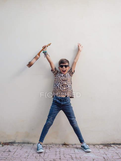 Cute joyful energetic cheerful child in denim and festive t-shirt having fun playing ukulele on background of white wall — Stock Photo