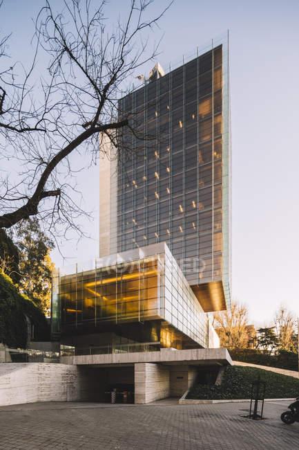 Stilvolles Glashochhaus mit Parkplätzen, die die Sonne bei hellem Tag in der Innenstadt reflektieren — Stockfoto