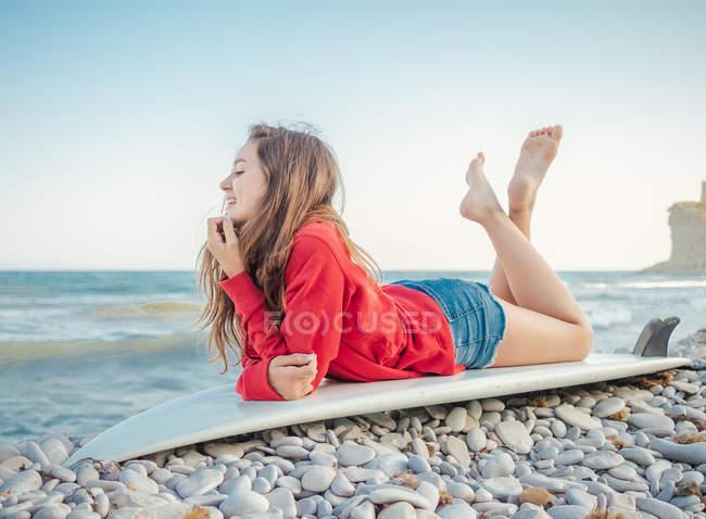 Приваблива усміхнена довга жінка з довгим волоссям у червоному капюшоні, яка лежить на дошці на кам