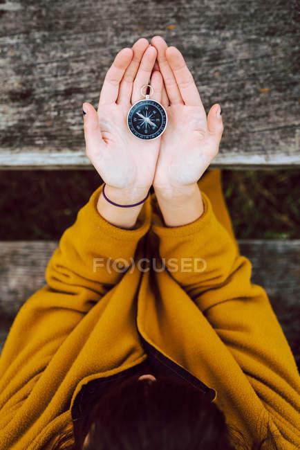 Imagen recortada de la mujer sosteniendo pequeña brújula vintage en las manos sobre la mesa de madera durante el viaje en el campo - foto de stock