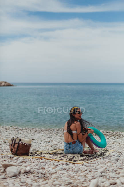 Back view of young brunette woman sitting at the beach holding a rubber ring — Stock Photo
