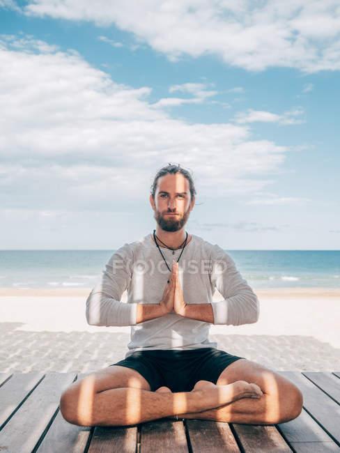 Взрослый бородатый мужчина, сидящий в позе лотоса на деревянном пирсе на берегу моря со скрещенными ногами и смотрящий в камеру — стоковое фото