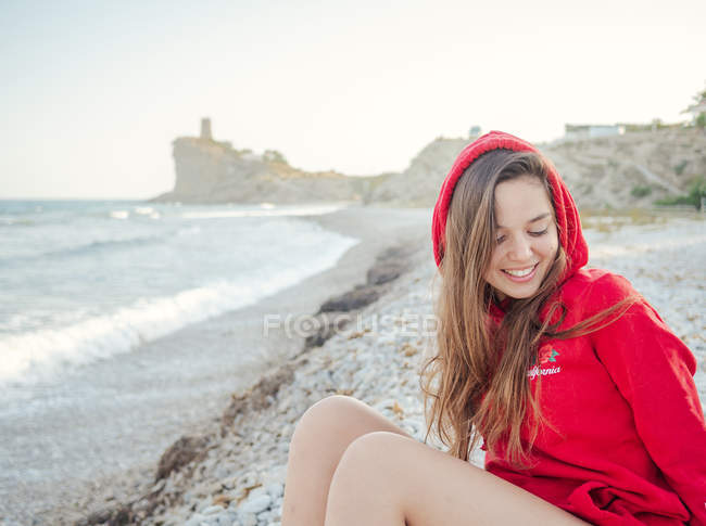 Charmante femme aux cheveux longs et au sweat à capuche rouge souriant et regardant vers le bas sur le bord de mer — Photo de stock