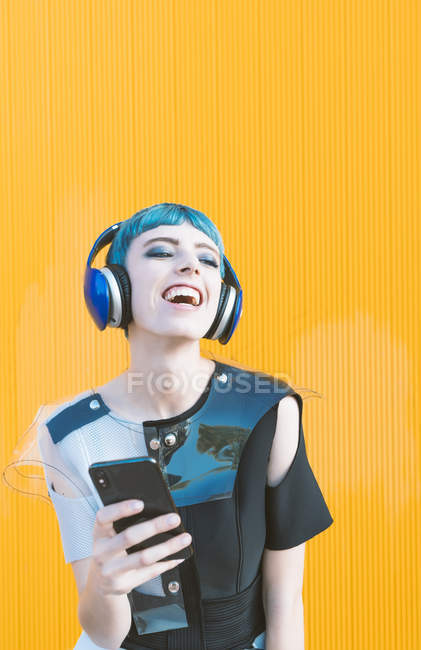 Cheerful informal woman in headphones and smartphone listening to music while standing against vivid yellow wall — Stock Photo