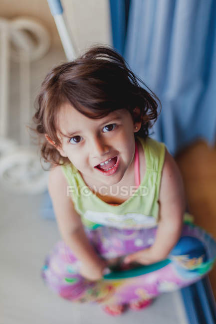 From above view of cheerful little girl looking at camera — Stock Photo