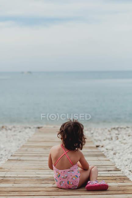 Вид сзади ребенка в розовом купальнике, сидящего на деревянной пристани у моря — стоковое фото