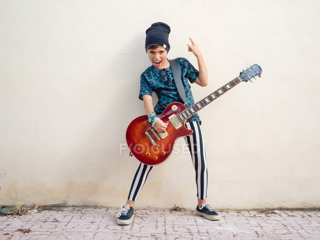 Cheeky active excited boy in colorful clothes playing guitar, showing two fingers up on background of white wall — Stock Photo