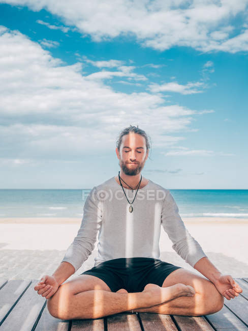 Adult bearded man meditating while sitting in lotus pose on wooden pier by seashore with legs crossed and closed eyes — Stock Photo