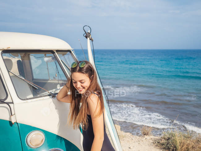 Woman smiling and looking down near white old fashioned car at seaside in bright serene day — Stock Photo