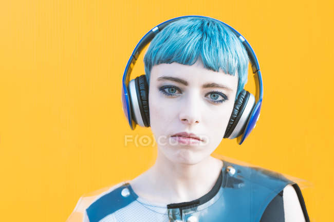 Cheerful young woman in trendy alternative dress smiling and listening to music in headphones against yellow wall — Stock Photo