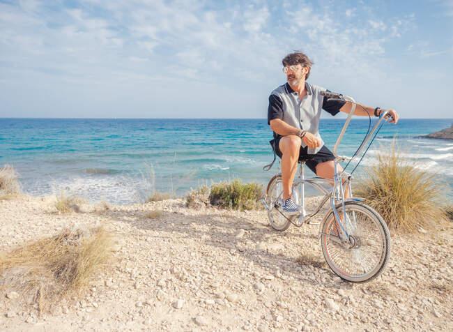 Зрелый бородатый спортсмен катается на велосипеде по морю с сухой травой на фоне удивительного бирюзового морского пейзажа в яркий день — стоковое фото