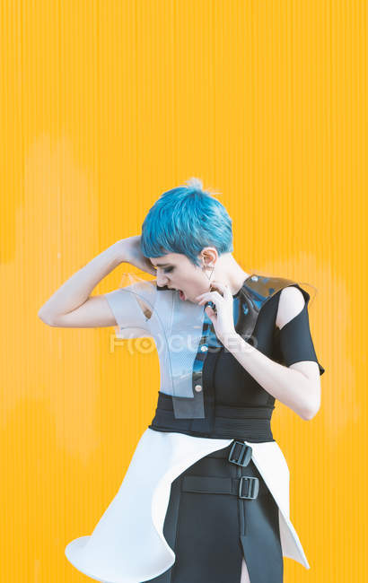 Sensual young woman in trendy futuristic dress screaming while standing on pavement against bright yellow wall — Stock Photo