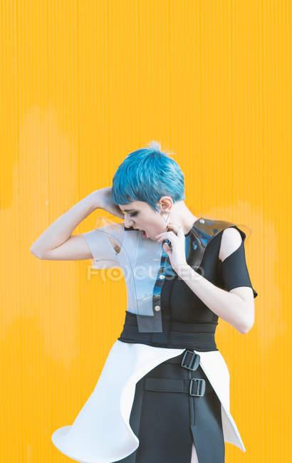 Sensual mujer joven en vestido futurista de moda gritando mientras está de pie en el pavimento contra la pared de color amarillo brillante - foto de stock
