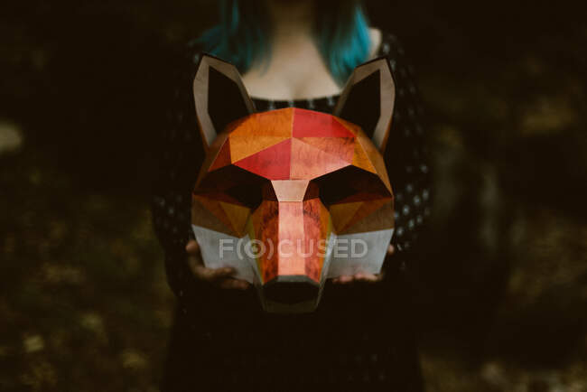 Anonymous female holding paper fox mask in mysterious autumn forest in overcast weather. Concept of wildlife habitat protection — Stock Photo