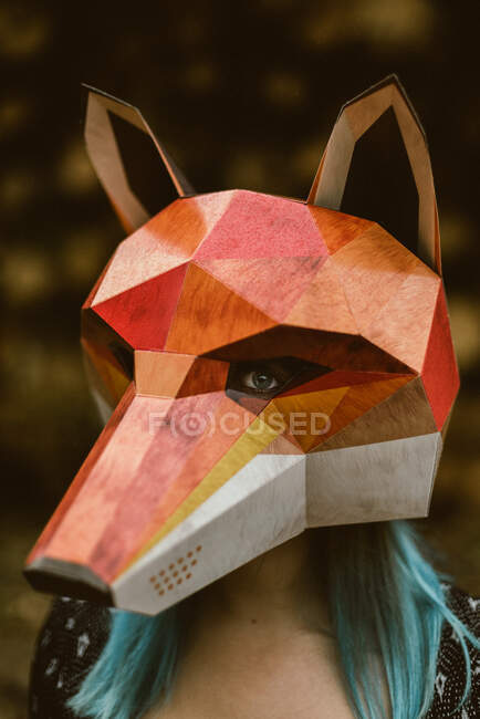 Anonymous female in paper fox mask covering full head looking away and standing on background with stack of logs. Concept of negative human impact on wildlife habitat — Stock Photo