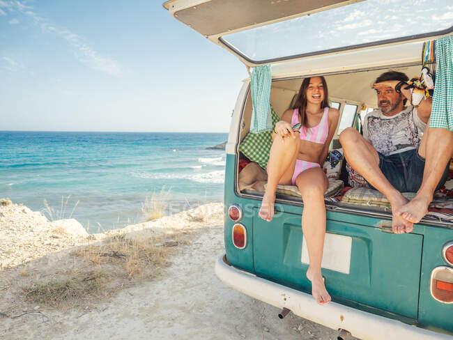 Затонула вродлива жінка з зрілим батьком сидить на відкритому багажнику трейлера на піщаному морі в яскравий день. — стокове фото