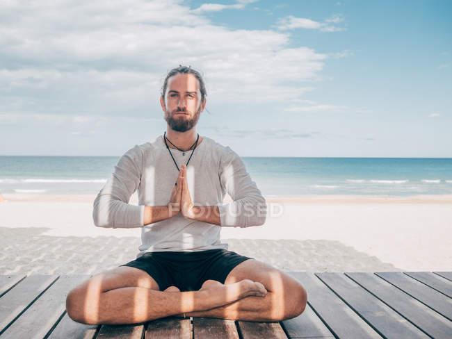 Взрослый бородатый мужчина медитирует, сидя в позе лотоса на деревянном пирсе у берега моря со скрещенными ногами и глядя в камеру — стоковое фото