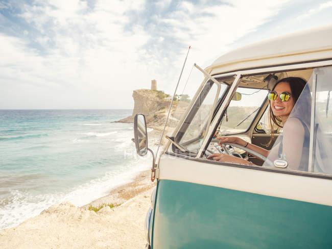 Вид сбоку на автомобиль с женщиной, рисующей на песчаном пустом пляже с пенными волнами в яркий солнечный день — стоковое фото