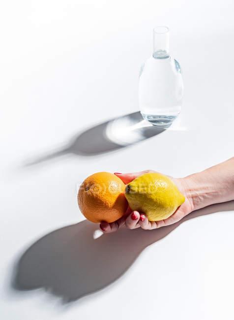 Primer plano de la mano femenina sosteniendo naranja madura y limón cerca de frasco transparente de agua sobre fondo blanco - foto de stock