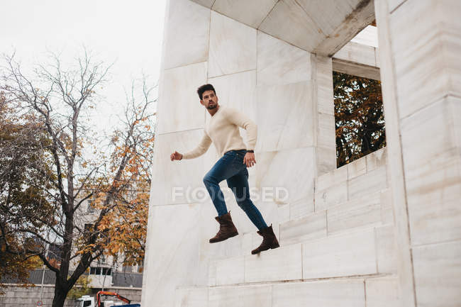 Trendy young man in jeans and white sweater running in air at white building — Stock Photo