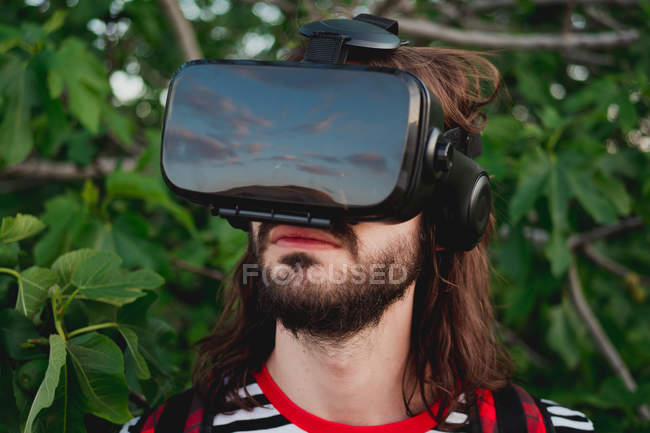 Side view of young cheerful male in virtual reality glasses exploring world in nature — Stock Photo