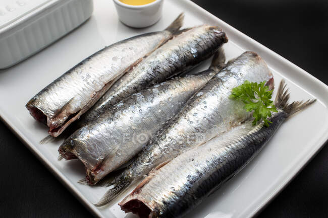 Fresh washed and scaled fish without heads on white plate — Stock Photo