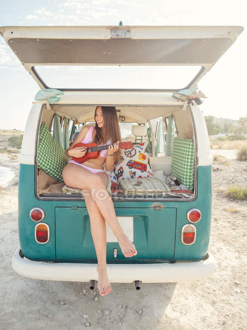 Mulher sorridente em maiô jogando ukulele enquanto sentado em travesseiro macio em van na natureza — Fotografia de Stock