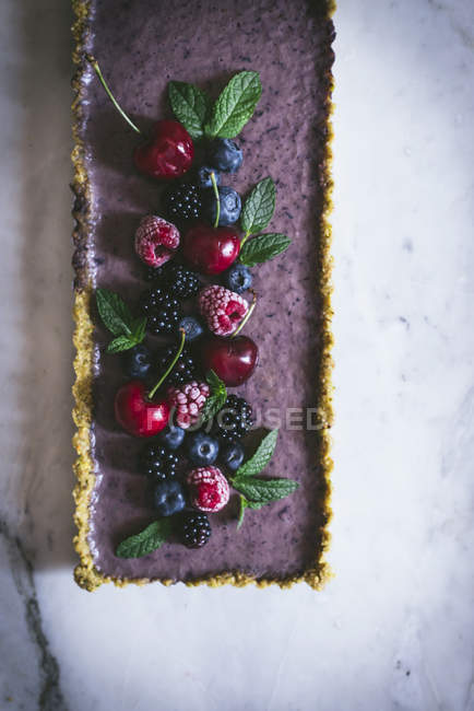 Tasty rectangular cake decorated with summer berries on white table — Stock Photo