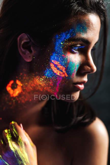 Вид сбоку на красивую молодую женщину, покрытую яркой краской на лице, шее и руке, смотрящую в сторону — стоковое фото
