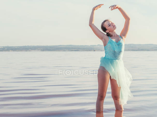 Ballerina  performing with raising hands in wavy water in bright sunny day — Stock Photo