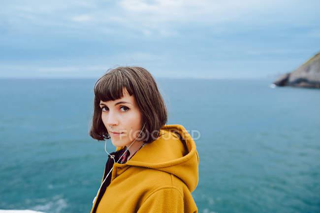 Жінка в жовтому теплому куртці дивиться на камеру, стоячи проти хвилястого моря і перевертаючи небо в природі — стокове фото