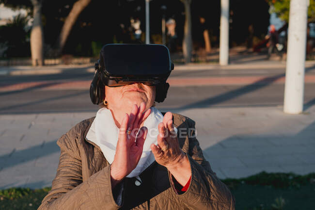 Forward-looking grandmother in virtual reality headset seeing new simulated world. Senior woman touching non-existent object with raised hand standing on blurred background with city street — Stock Photo