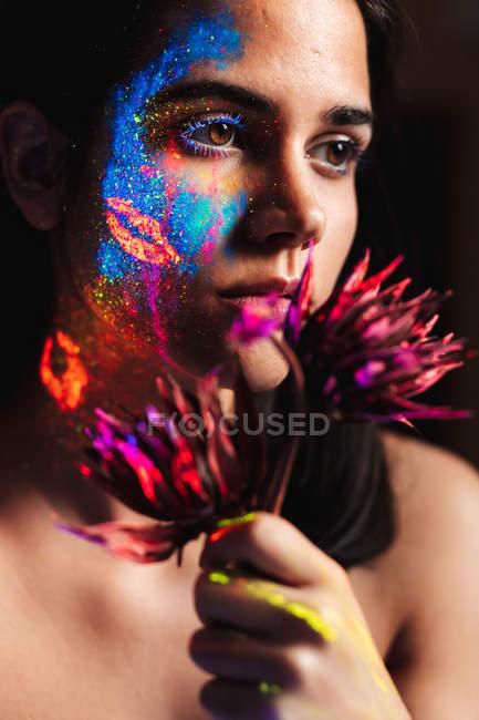 Ritratto di bella giovane donna ricoperta di vernice luminosa sul viso che tiene un fiore e distoglie lo sguardo — Foto stock