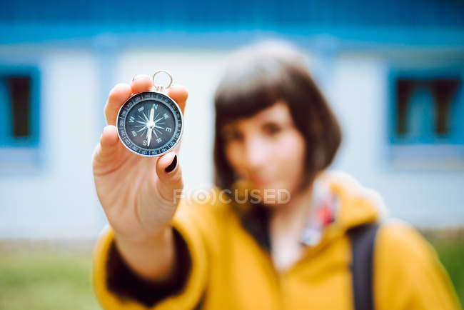 Cheerful blur young woman holding retro compass near face while standing on blurred background of countryside house — Stock Photo
