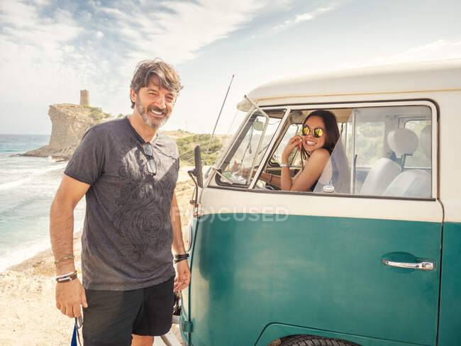 Kind smiling man and pretty woman laughing in front seat of car in desert place looking at camera — Stock Photo