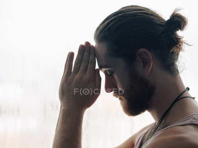 Relaxed thoughtful man in harmony with praying hands in forehead near steamy windows with closed eyes — Stock Photo