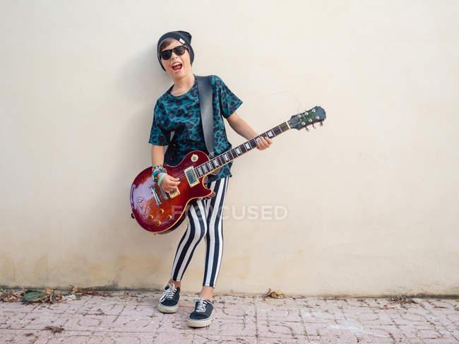 Frech aktiv aufgeregt fröhlicher Junge in bunten Kleidern spielt Gitarre auf dem Hintergrund der weißen Wand — Stockfoto