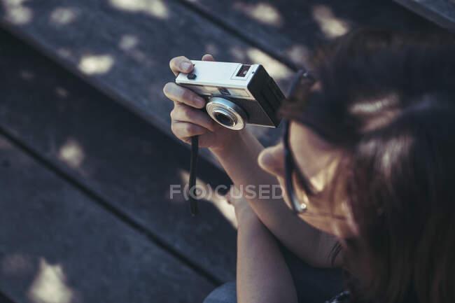 З висоти довгий волосий молодий фотограф ховає фотоапарат і чекає на фото, сидячи на лавці в яскравий контрастний день. — стокове фото