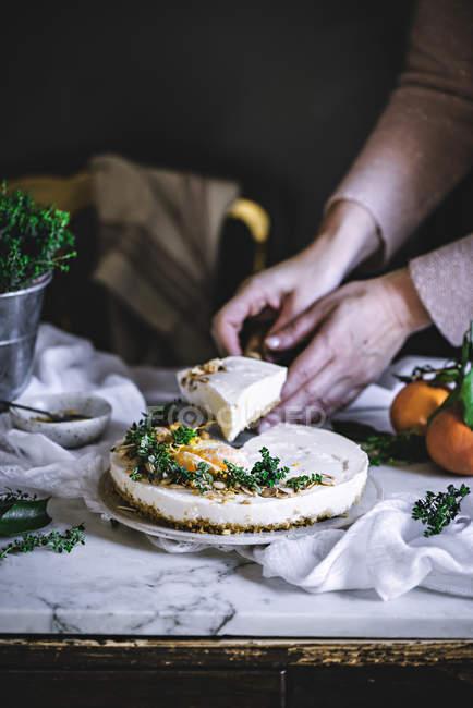 Plan rapproché des mains femelles prenant la tranche du gâteau crémeux de mandarine sur le tissu blanc — Photo de stock
