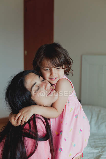 Happy young brunette female with kid embracing with closed eyes bed at home — Stock Photo