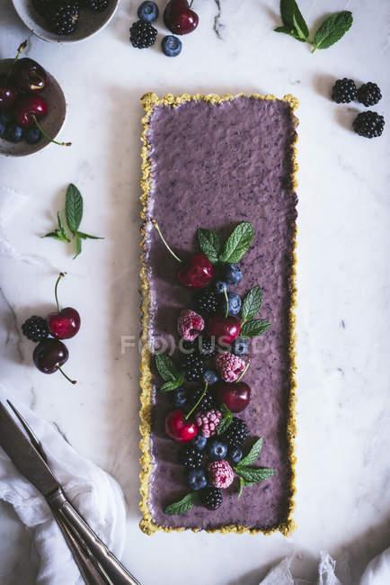 Вкусный прямоугольный торт украшенный летними ягодами на белом столе — стоковое фото