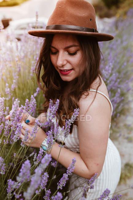 Приваблива жінка з довгим волоссям у капелюсі насолоджується лавандою і посміхається закритими очима. — стокове фото