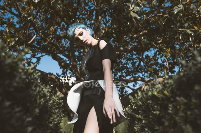 Знизу молода жінка в футуристичному вбранні дивиться на камеру, стоячи біля дерев у тумані. — стокове фото