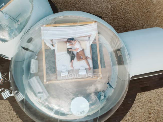 Luftaufnahme von leidenschaftlichem Paar, das in Bubble Hotel auf dem Bett liegt — Stockfoto